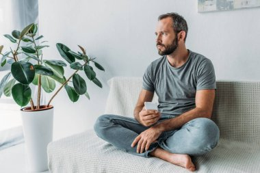 upset bearded man holding smartphone and looking away while sitting on couch at home