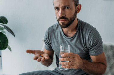 bearded middle aged man looking at camera while holding pills and glass of water
