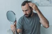 vousatý středního věku muž s alopecie pohledu na zrcadlo, koncept vypadávání vlasů