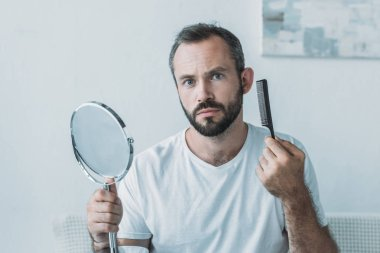 middle aged man holding mirror with comb and looking at camera, hair loss concept