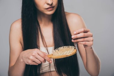 cropped shot of young brunette woman combing hair with hairbrush isolated on grey, hair loss concept