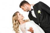 krásná mladá nevěsta a ženich všeobjímající během tance a při pohledu na sebe izolované na bílém