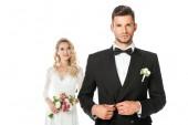 Fotografia bello giovane sposo abbottona la giacca e che guarda lobbiettivo con la sposa in piedi vaga su fondo isolato su bianco