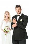 Fotografie handsome young groom buttoning cufflink and looking at camera with bride standing blurred on background isolated on white