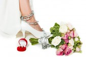 Fotografie cropped shot of bride with leg tied in chain standing near bouquet and wedding rings isolated on white