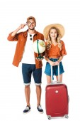 smiling couple standing with magnifying glass, globe and travel bag isolated on white