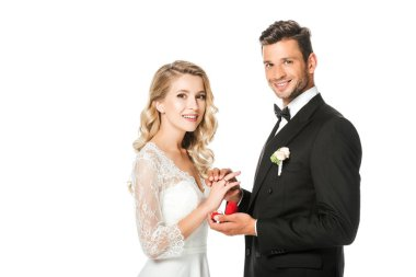 happy groom putting on wedding ring on brides finger and looking at camera isolated on white
