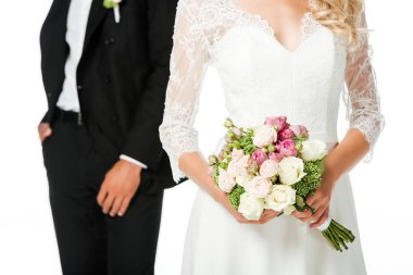 cropped shot of bride with bouquet and groom isolated on white