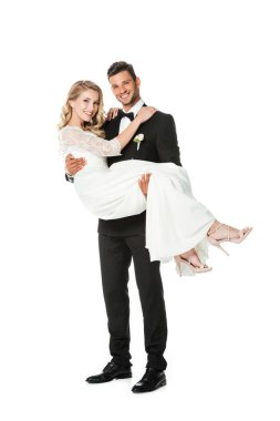 handsome young groom carrying his bride isolated on white