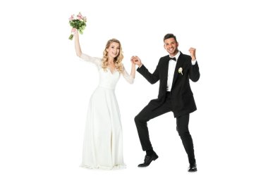 beautiful young bride and groom dancing and looking at camera isolated on white