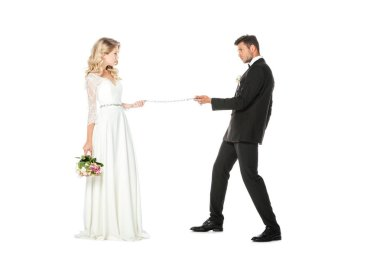 young groom with chain and leashed bride looking at each other isolated on white