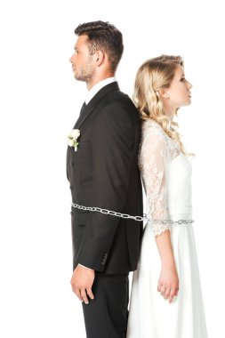 young newlyweds tied with chain back to back isolated on white