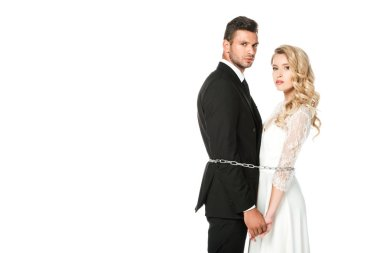 serious young newlyweds tied with chain and looking at camera isolated on white