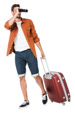 Happy young man with binoculars and luggage walking and looking away isolated on white stock vector