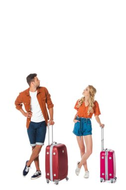 young couple with luggage looking up isolated on white