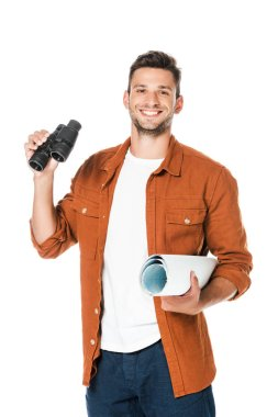 happy young man with binoculars and rolled map looking at camera isolated on white