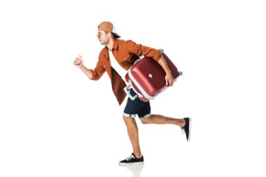 side view of handsome man running with luggage isolated on white