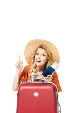 beautiful girl holding passport witch ticket and pointing up isolated on white