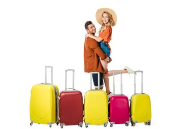 side view of man holding girlfriend on hands with suitcases around isolated on white