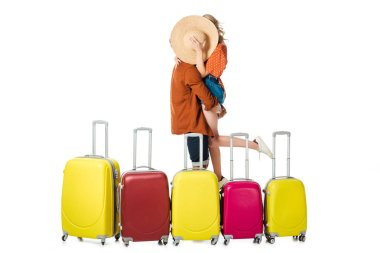 obscured view of newlywed couple kissing behind straw hat with arranged suitcases around isolated on white