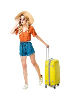 Shocked woman in sunglasses and straw hat with yellow suitcase isolated on white stock vector