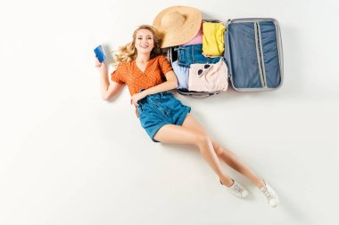 overhead view of young smiling woman with passport and ticket in hand lying on suitcase