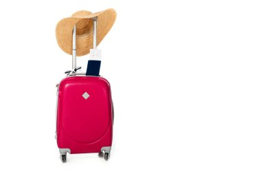 close up view of pink suitcase, straw hat, passport and ticket isolated on white