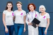 Fotografia donne e medico con nastri rosa che stanno insieme e sorride alla macchina fotografica, concetto di consapevolezza del cancro al seno