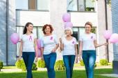 Fotografia donne sorridenti che tiene i palloni rosa e camminare insieme, concetto di consapevolezza del cancro al seno
