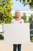 Fotografie senior woman with pink ribbon holding blank banner and looking at camera, breast cancer awareness concept