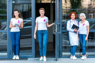 women and doctor with pink ribbons standing near modern building and smiling at camera, breast cancer awareness concept