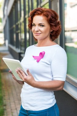 Smiling middle aged woman with pink ribbon using digital tablet and looking away, breast cancer awareness concept stock vector