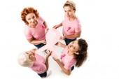 Fotografia punto di vista ambientale delle donne in rosa t-shirt che tiene nastro di consapevolezza del cancro al seno e che sorride alla macchina fotografica isolata su bianco