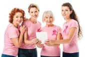 Fotografia donne in t-shirt rosa con nastri di consapevolezza del cancro al seno che tiene compressa digitale e che sorride alla macchina fotografica isolata su bianco