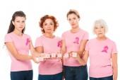 ženy v růžová trička s prsu rakovina povědomí pásky drží kostky s slovo rakovina a při pohledu na fotoaparát izolované na bílém