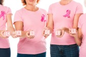 cropped shot of women in pink t-shirts with breast cancer awareness ribbons holding cubes with word cancer isolated on white