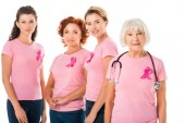 women in pink t-shirts with breast cancer awareness ribbons and senior doctor with stethoscope smiling at camera isolated on white