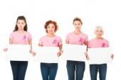Fotografia donne in t-shirt rosa con nastri di consapevolezza di cancro di seno che tengono le schede in bianco e che guarda lobbiettivo isolato su bianco