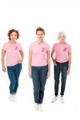 Fotografia donne in t-shirt rosa con nastri di consapevolezza del cancro al seno che guarda lobbiettivo isolato su bianco