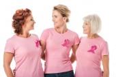Fotografia donne con nastri rosa che stanno insieme e sorridente ogni altro isolato su bianco, concetto di consapevolezza del cancro al seno