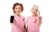 Fotografia donne con nastri rosa utilizzando smartphone e sorride alla macchina fotografica isolato su bianco, concetto di consapevolezza del cancro al seno