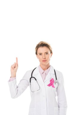 doctor with pink ribbon pointing up with finger and looking at camera isolated on white, breast cancer awareness concept