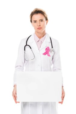 doctor with pink ribbon holding blank banner and looking at camera isolated on white, breast cancer awareness concept