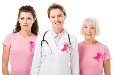 doctor and women with breast cancer awareness ribbons smiling at camera isolated on white