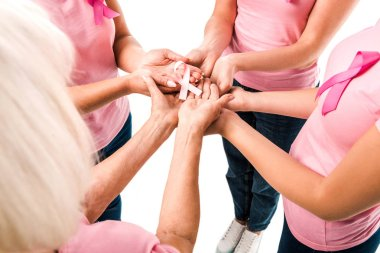partial view of women in pink t-shirts holding breast cancer awareness ribbon isolated on white