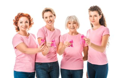 women in pink t-shirts holding breast cancer awareness ribbons and smiling at camera isolated on white