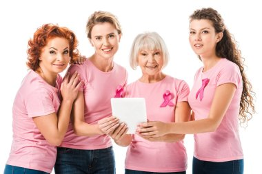 Women in pink t-shirts with breast cancer awareness ribbons holding digital tablet and smiling at camera isolated on white stock vector