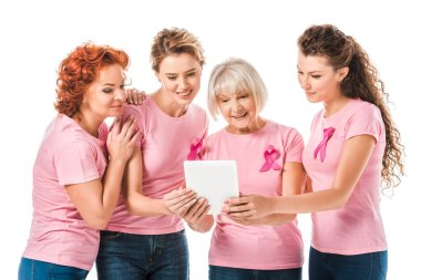 Smiling women in pink t-shirts with breast cancer awareness ribbons using digital tablet isolated on white stock vector