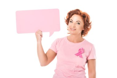 middle aged woman in pink t-shirt with breast cancer awareness ribbon holding blank speech bubble and smiling at camera isolated on white
