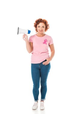 woman in pink t-shirt with breast cancer awareness ribbon holding megaphone and smiling at camera isolated on white